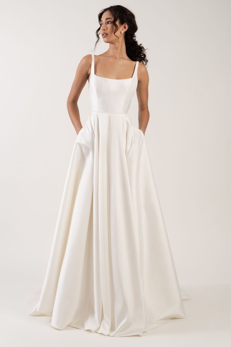 Model in long white wedding gown with pockets