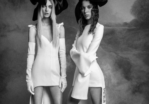 Two models in high-low white dresses and black bow headpieces