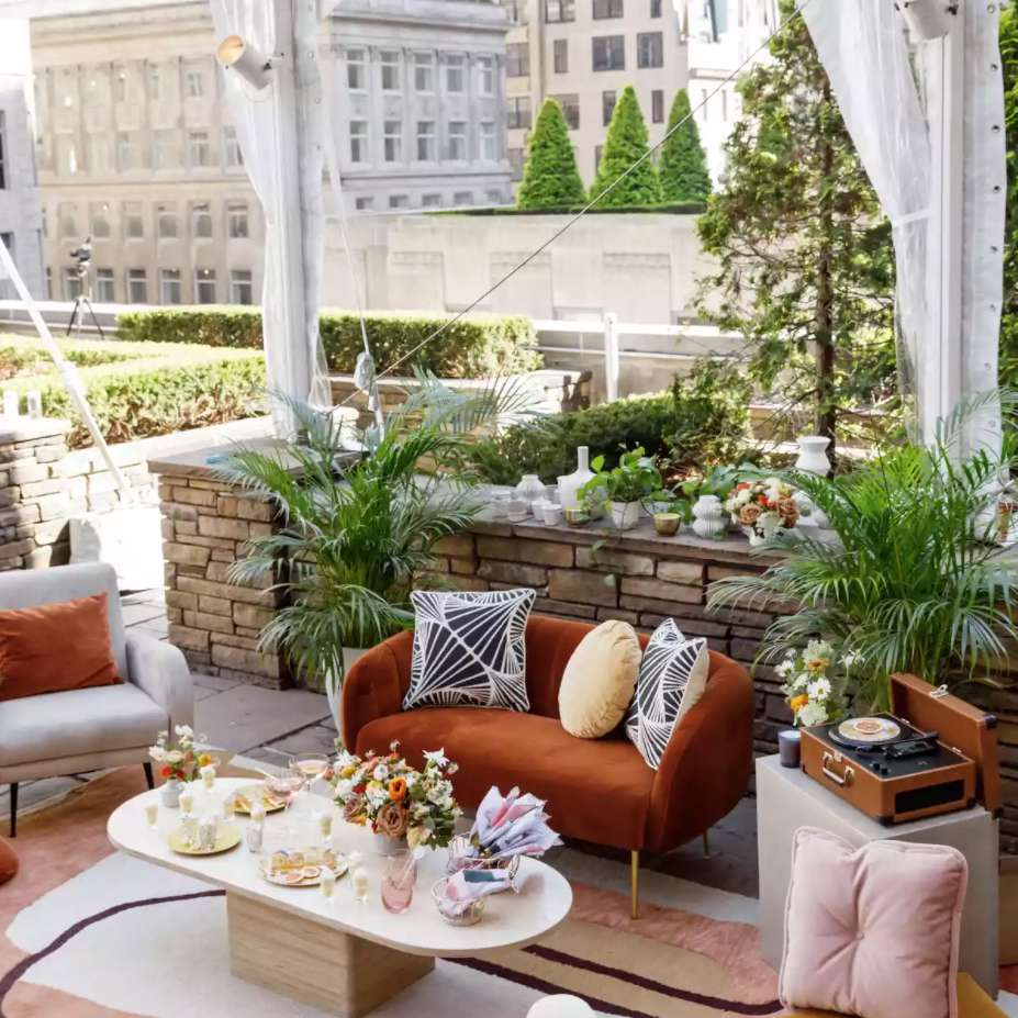 Lounge area with burnt orange furniture and florals