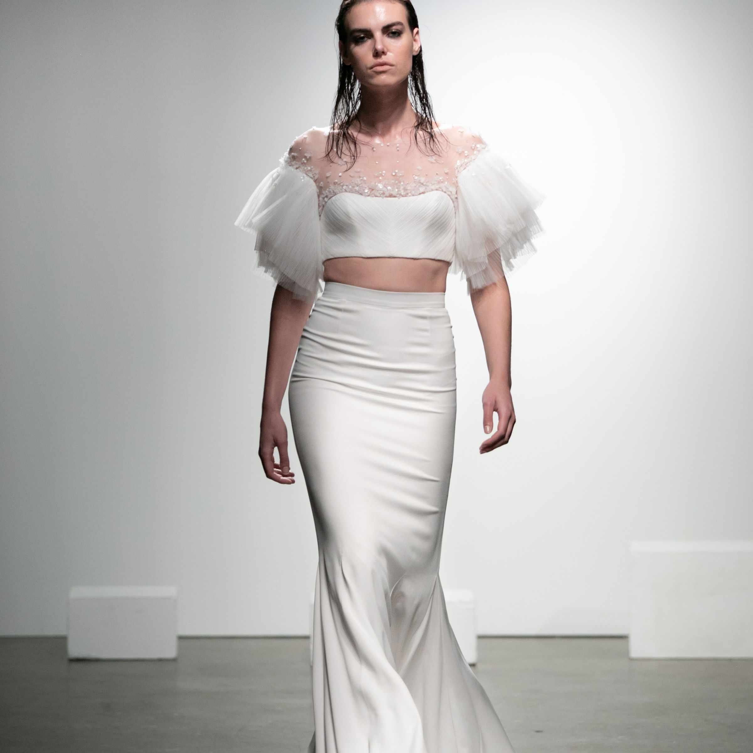 Model in crop top with tulle sleeves and embroidered tulle neckline and long skirt
