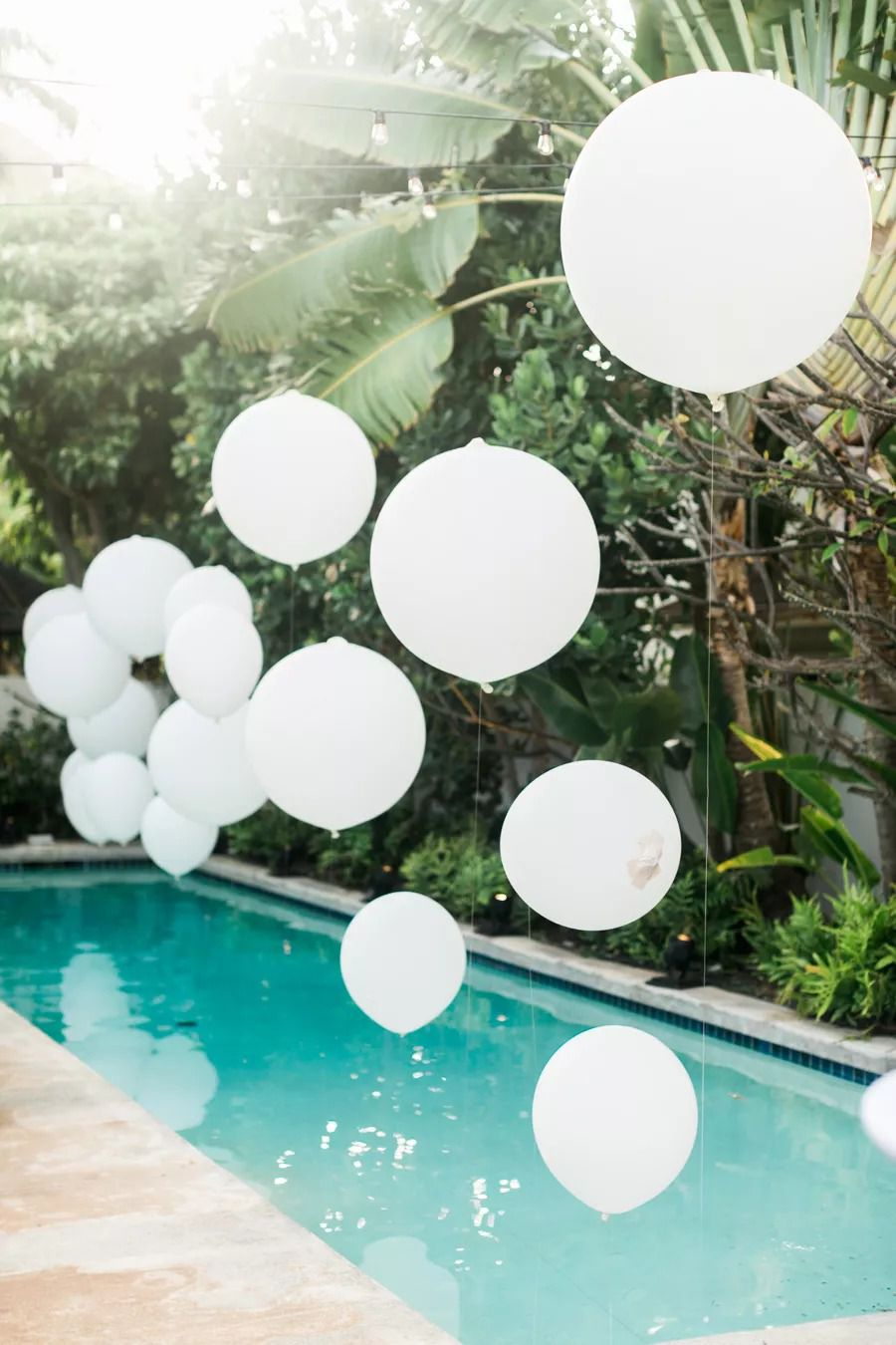 White balloons floating over a pool