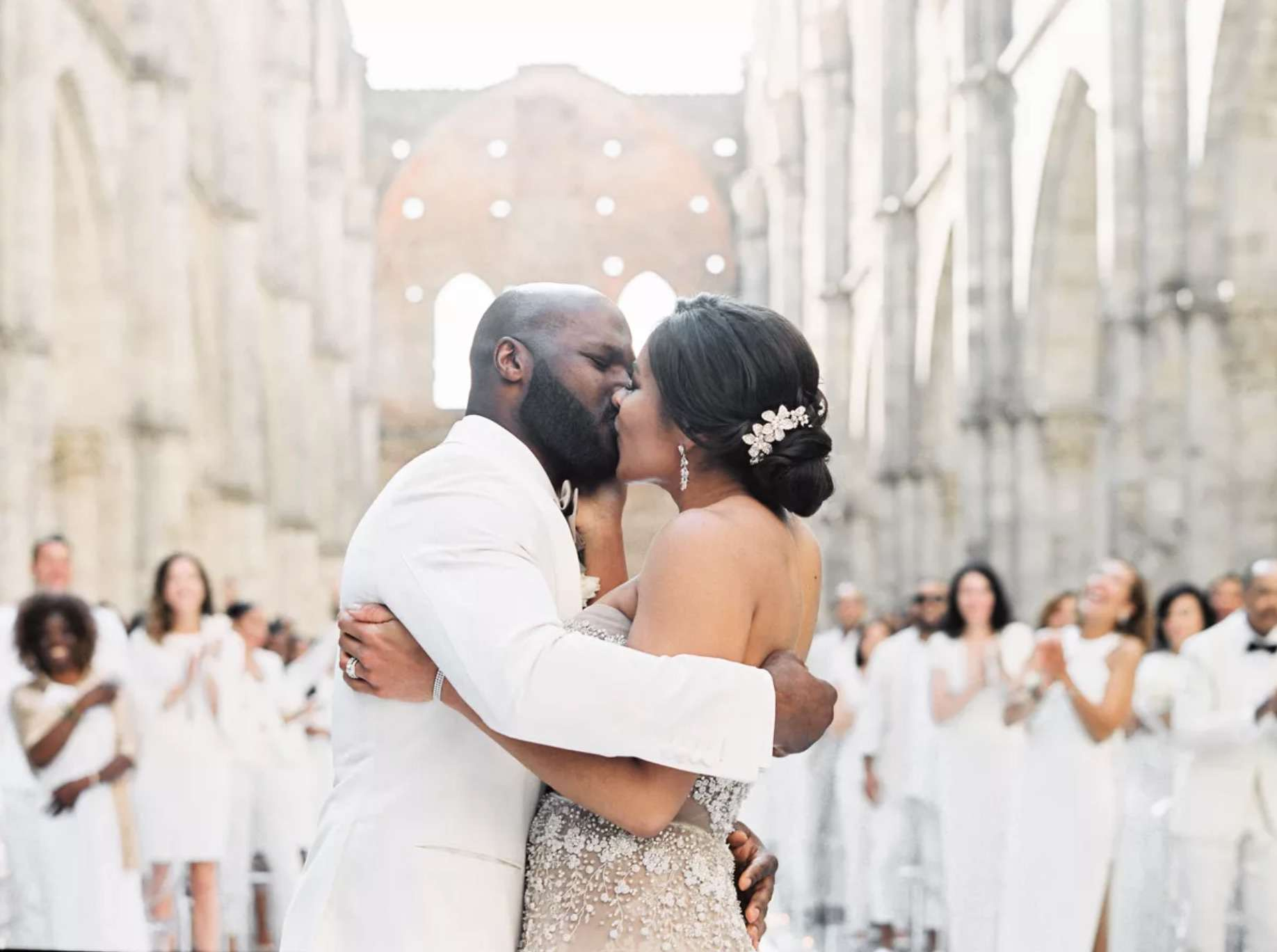 Newlyweds kissing in front of guests in white