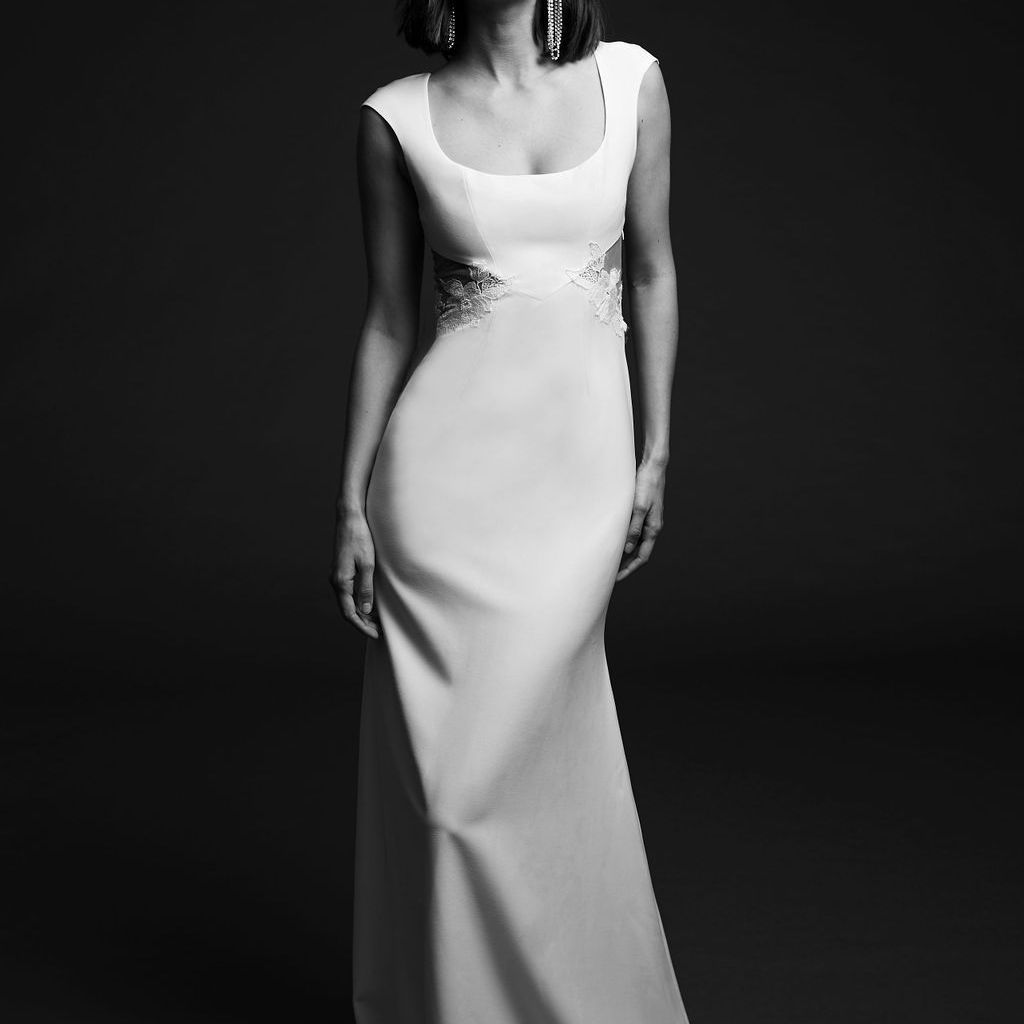 Model in fitted crepe dress with scoop neck, cap sleeves, and illusion side cutouts with floral embroidery