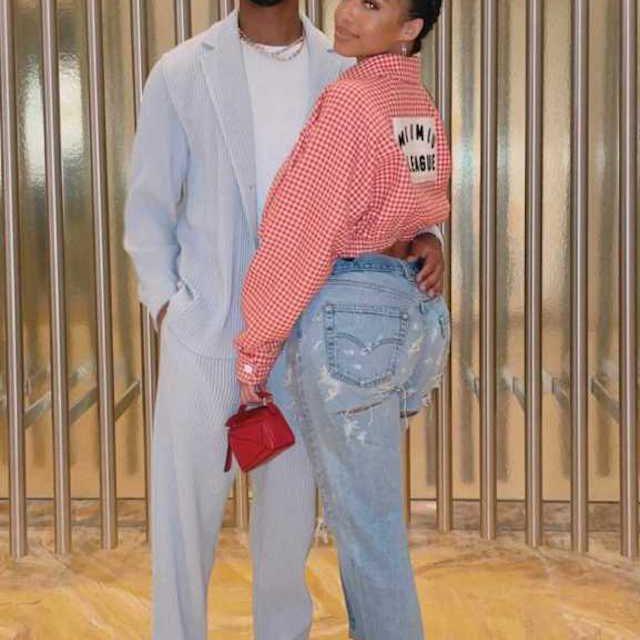 Michael B. Jordan wears a light blue suit and holds the waist of girlfriend Lori Harvey.