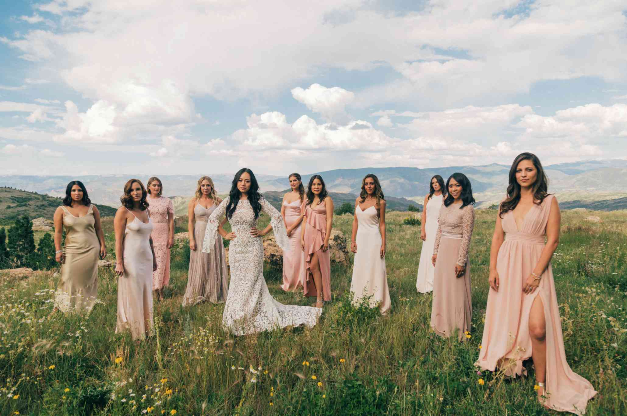 Bride and bridesmaids posing in front of mountain panorama
