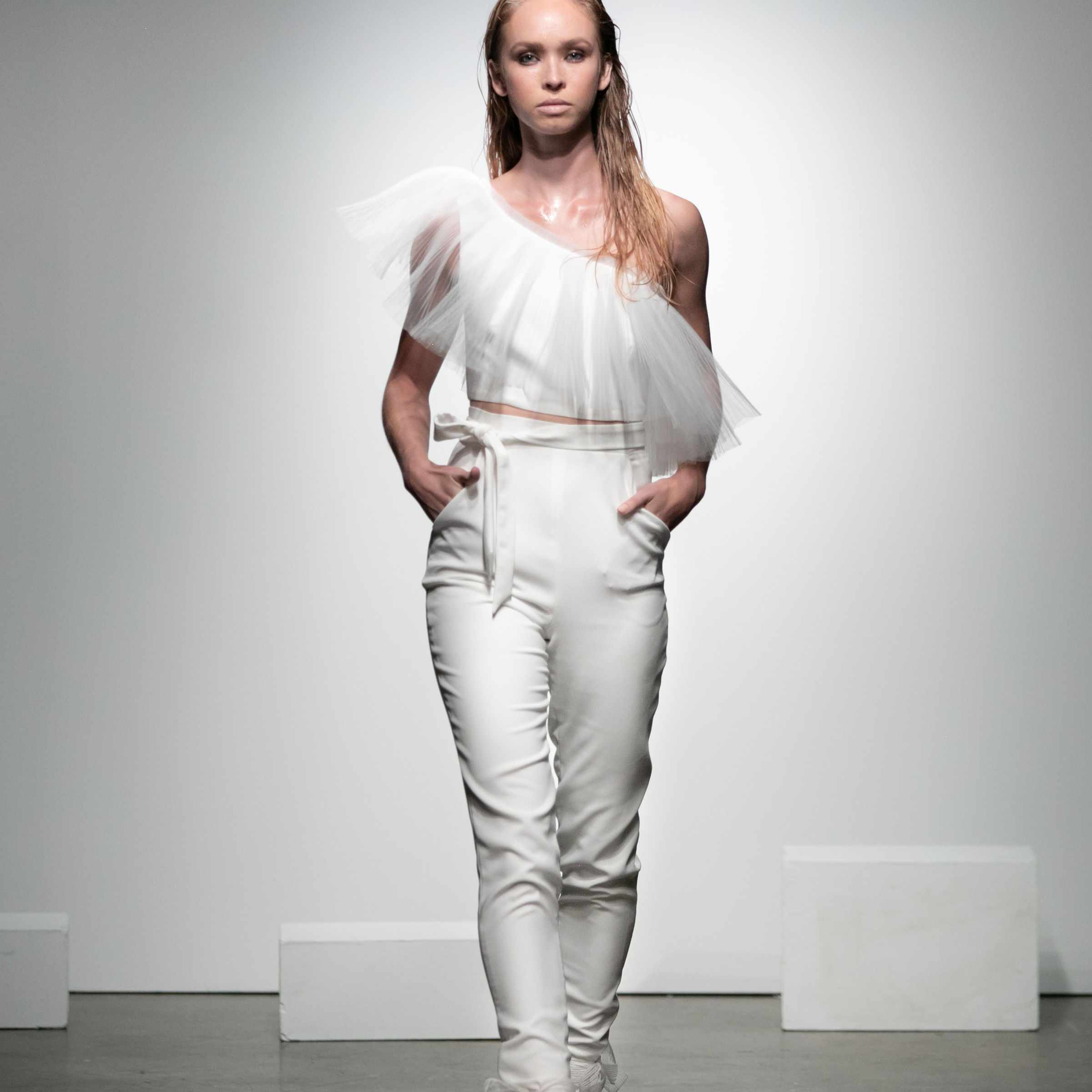 Model in two-piece jumpsuit with asymmetrical tulle top