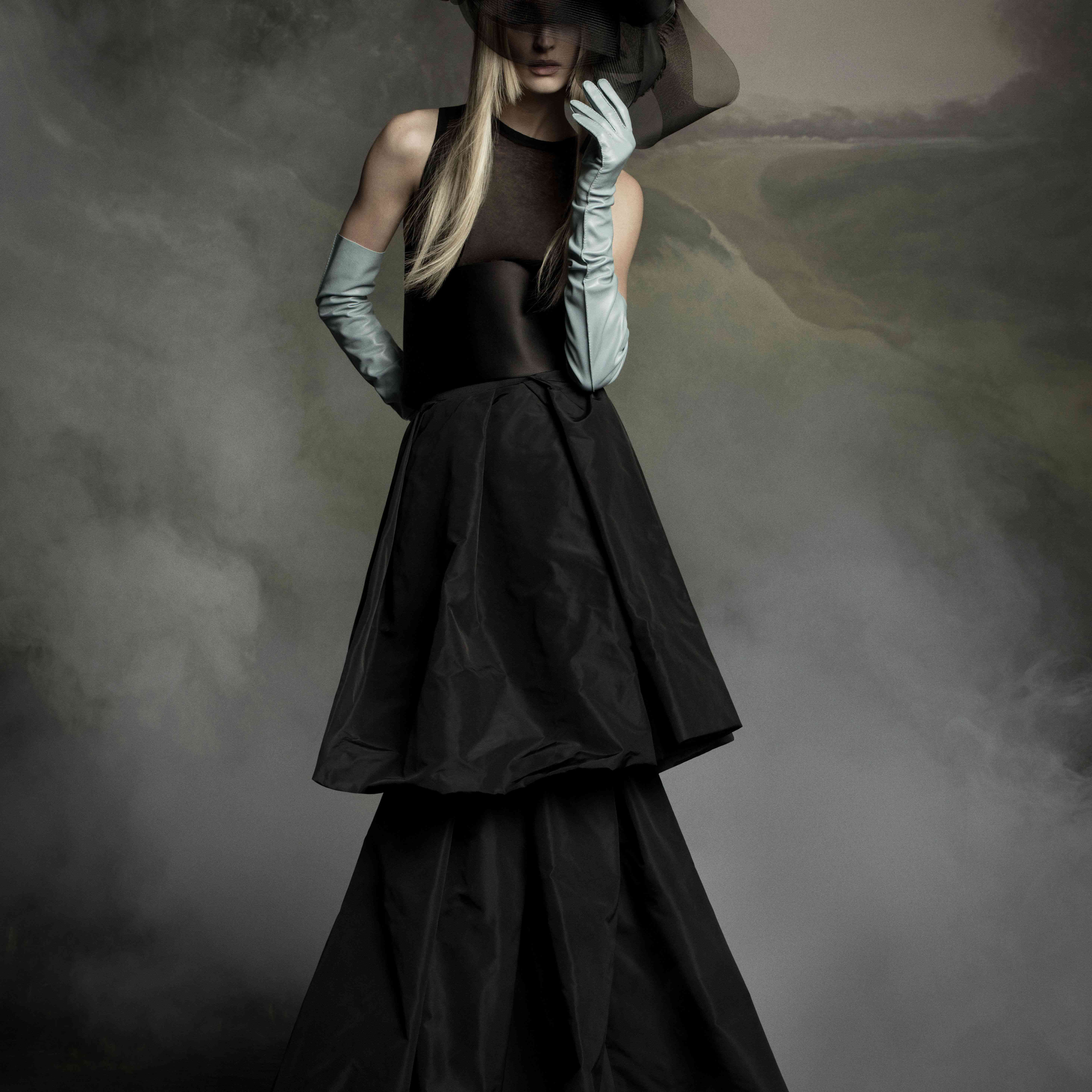 Model in two-tiered black gown with a black headpiece