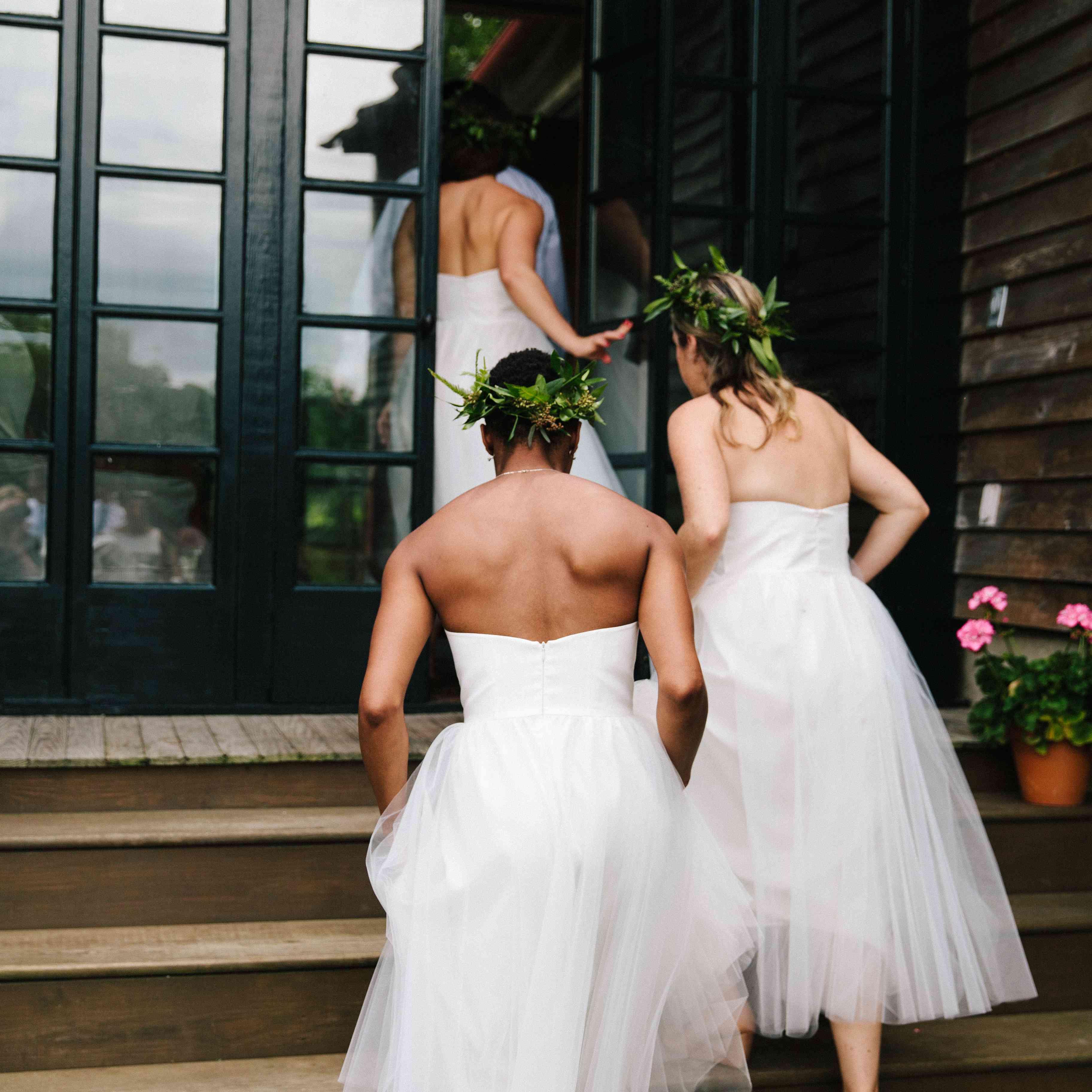bridesmaids in white walking up stairs
