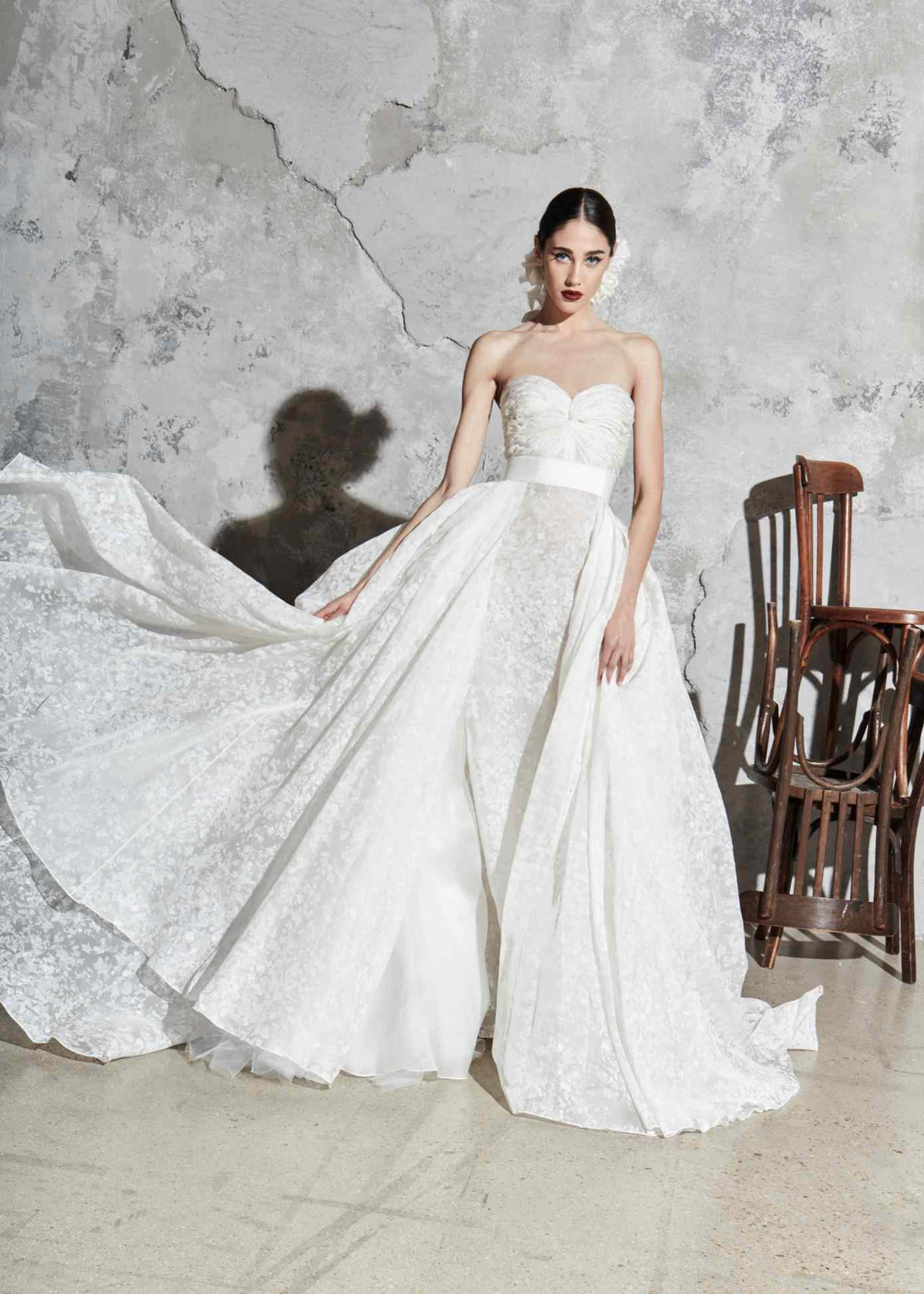 Model in a strapless floral ballgown with a voluminous overskirt and a white waistband