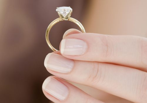 A woman's hand holding an engagement ring.