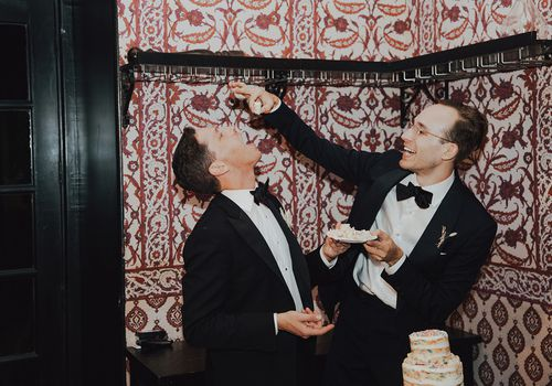 Same-sex couple feeding each other wedding cake in an intimate indoor reception