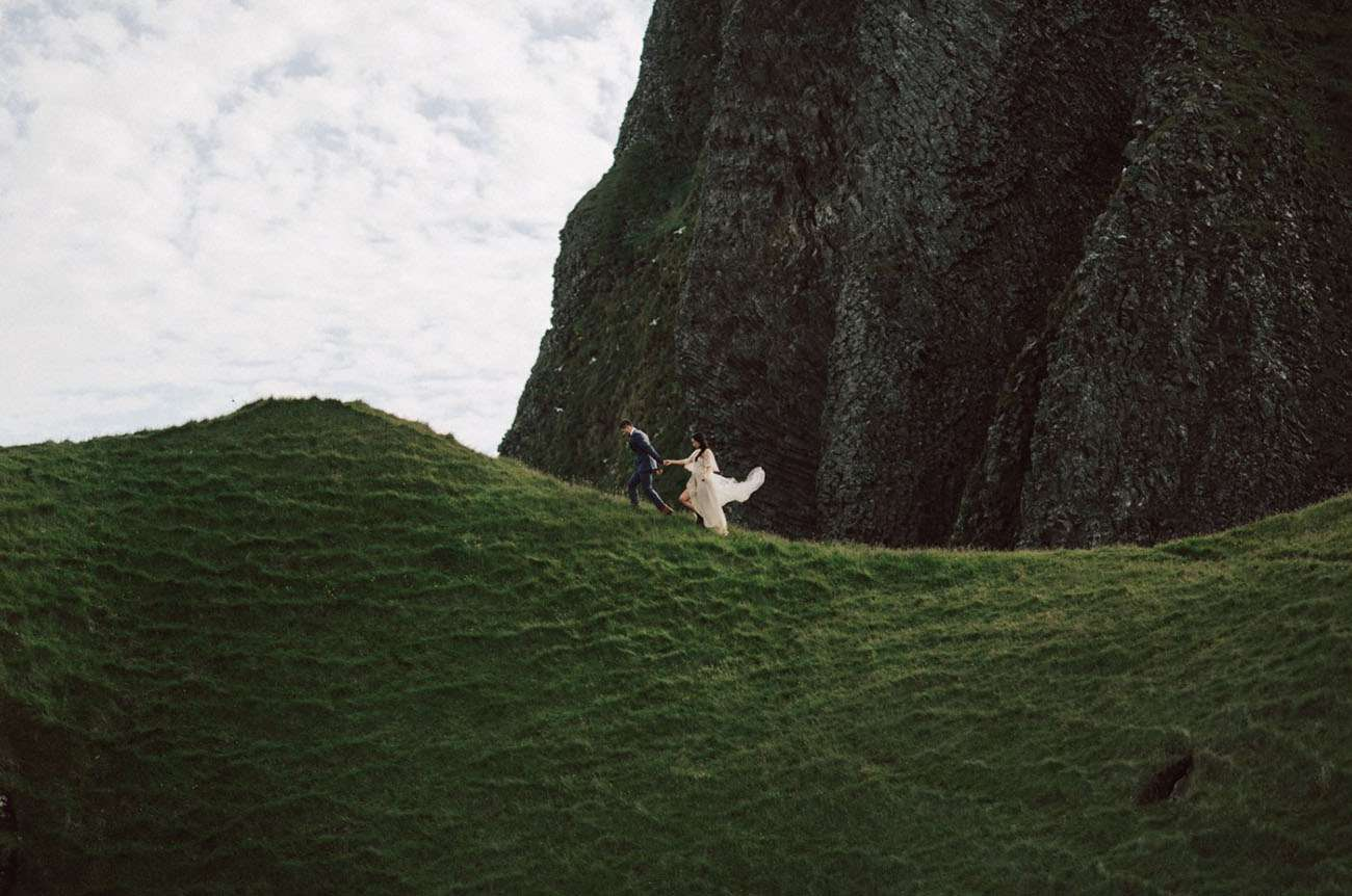 Couple walking in the grass in Iceland