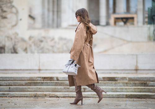 a woman in a trench coat walking on a sidewalk
