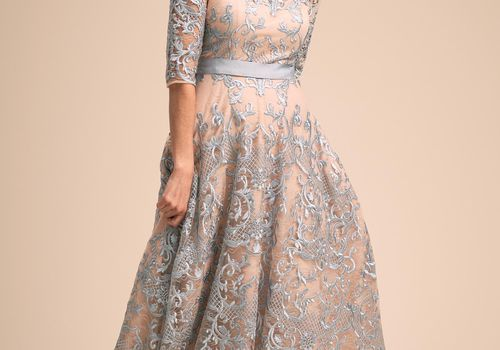 Light blue tea-length dress with embroidered floral embellishments and a satin ribbon