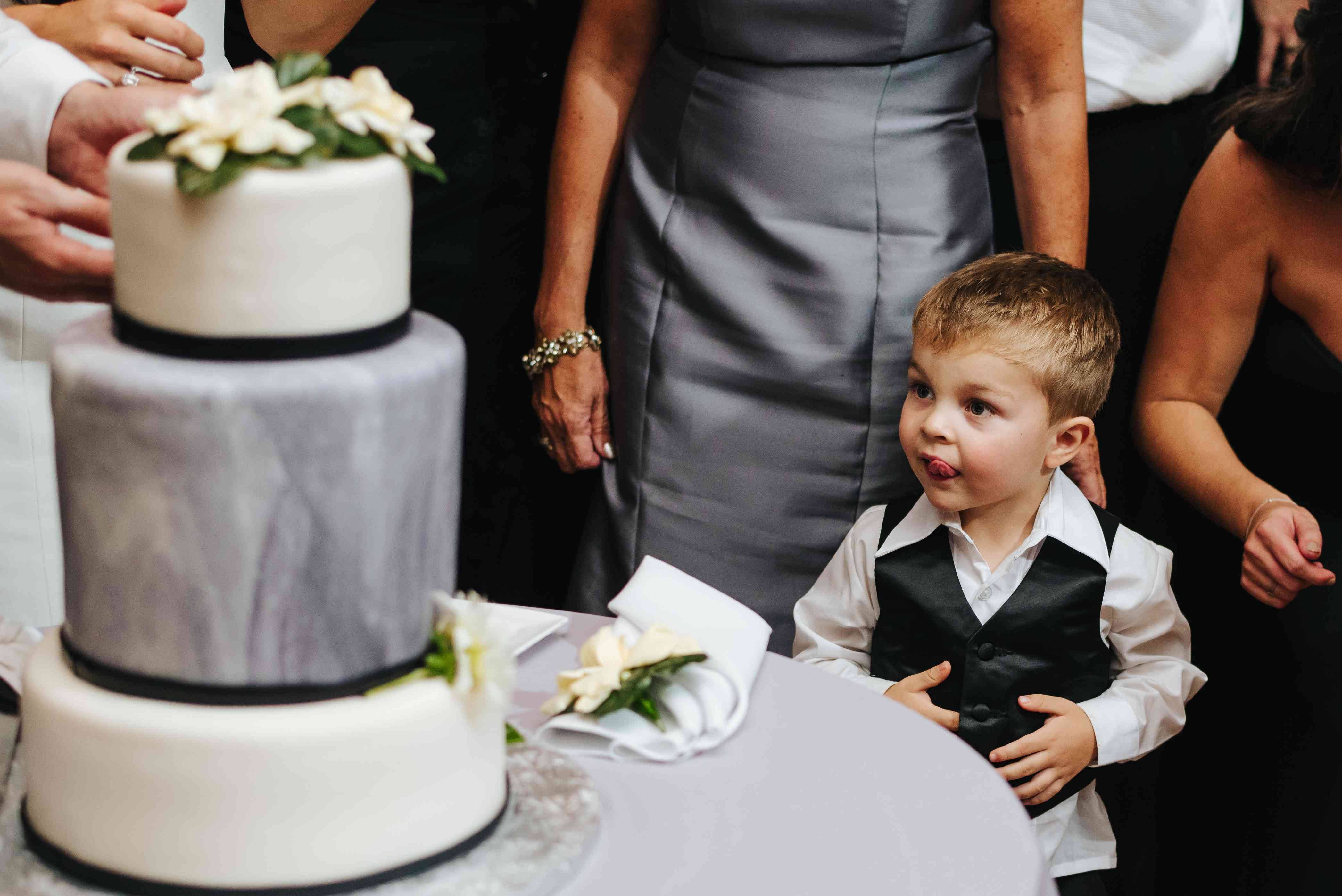 cutting the cake with kids at wedding with ring bearer