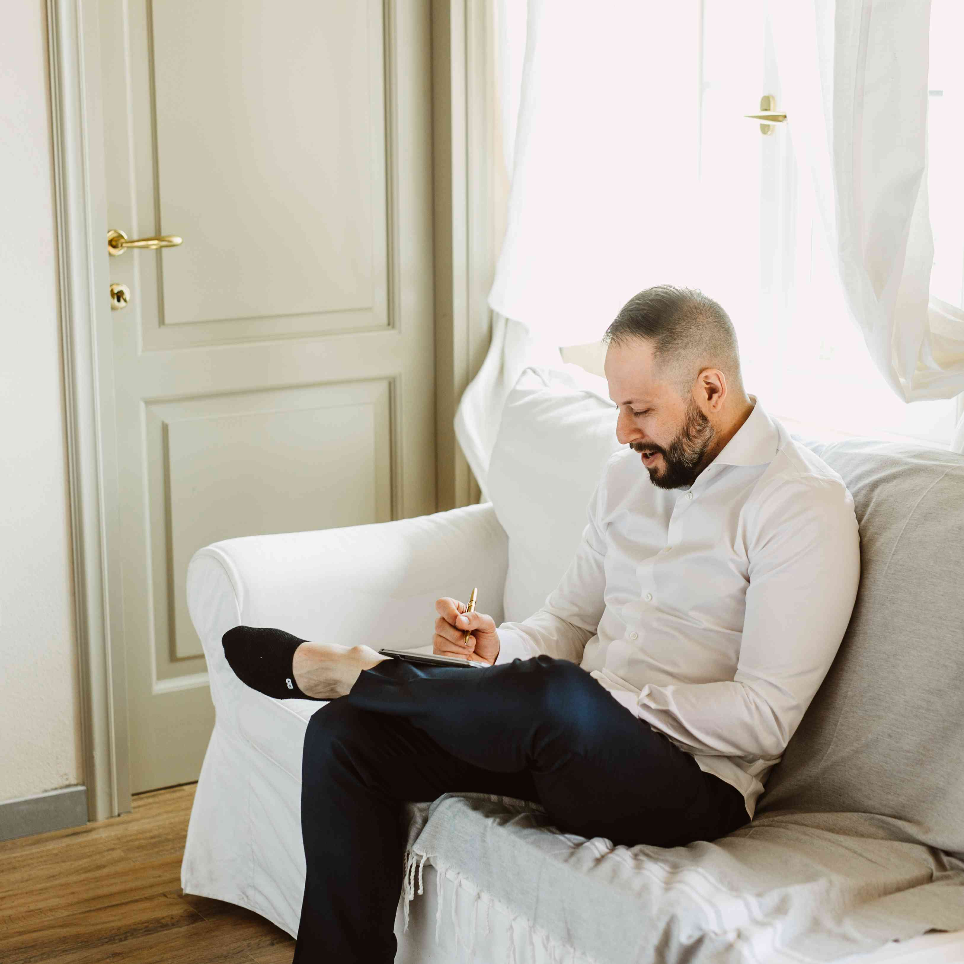 Man sitting on couch signing paperwork