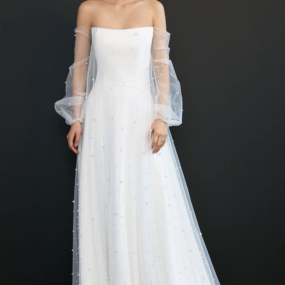 Model in wedding gown with sheer off-the-shoulder long sleeves