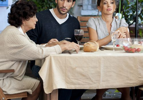 Young couple dining with mother in law, young woman has unhappy expression