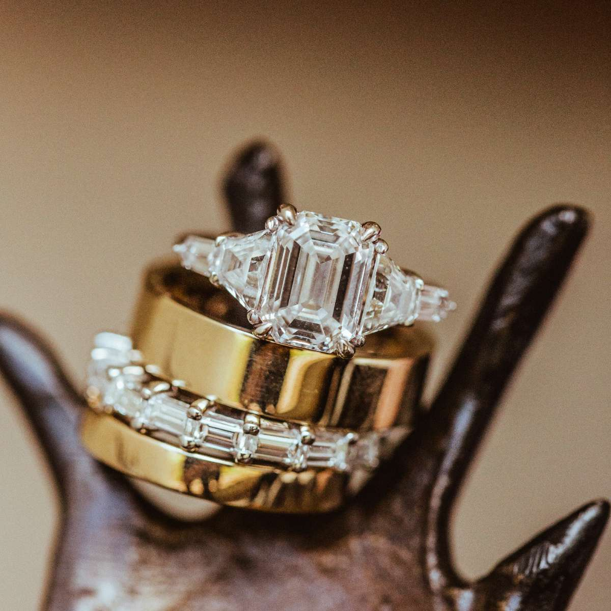A diamond engagement ring and baguette diamond wedding band with two gold bands on ring holder
