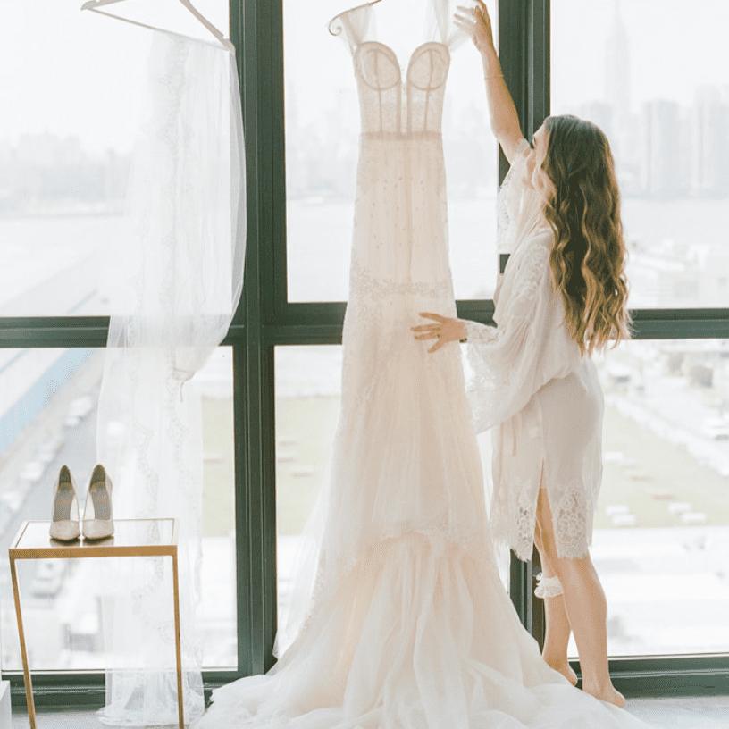 Bride hanging wedding dress