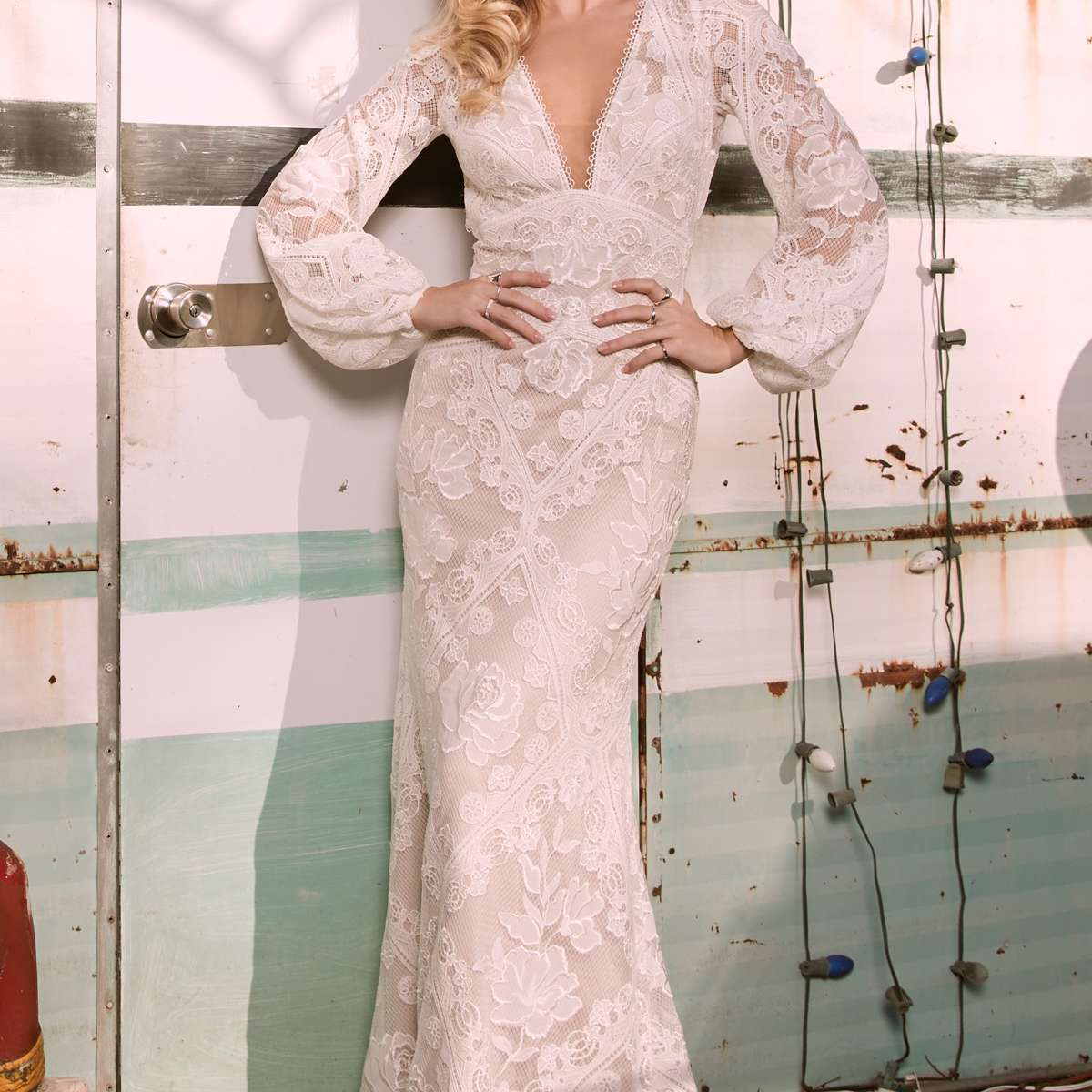 Model in allover lace plunging neckline empire waist fit-and-flare gown with long puffy sleeves