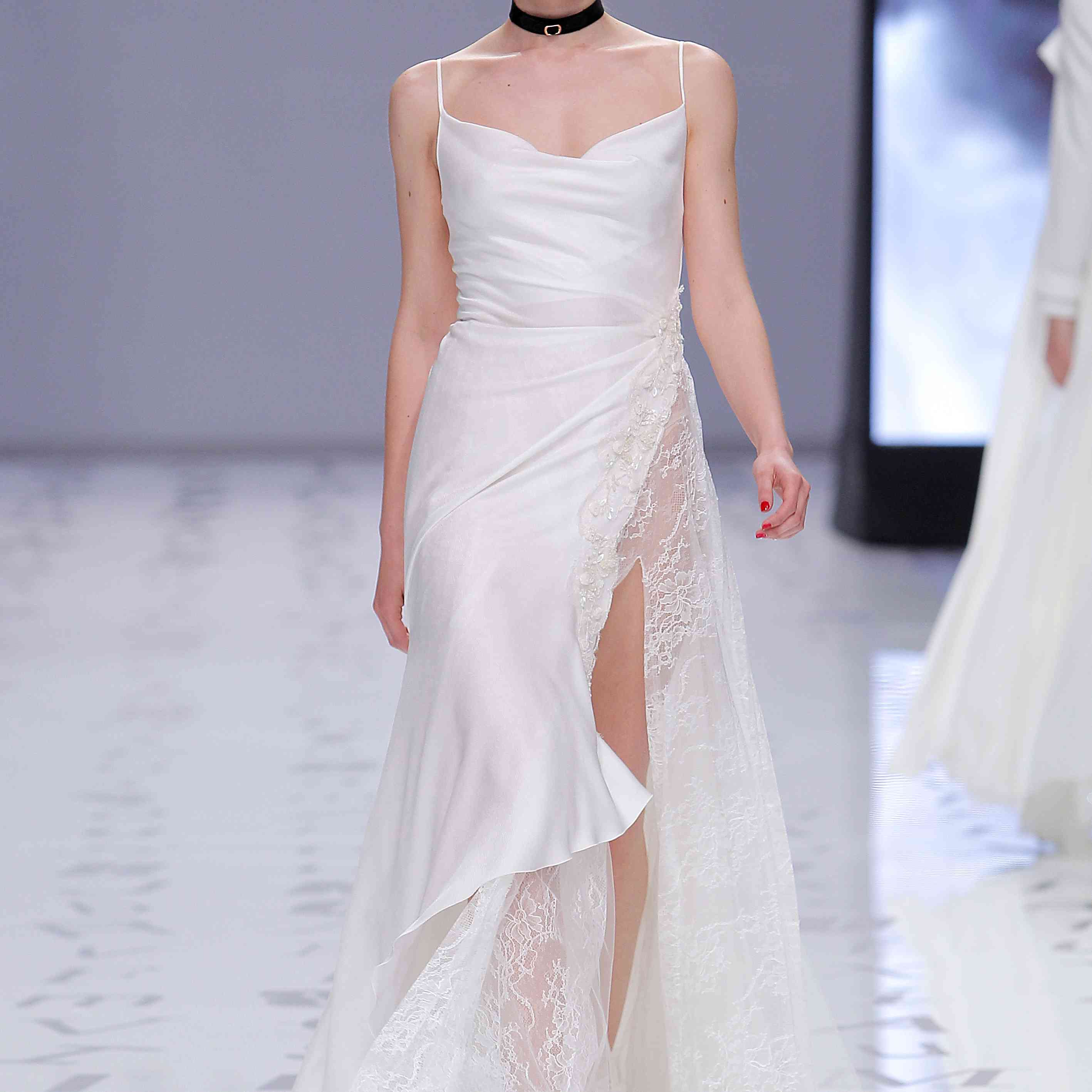 Model in satin A-line dress with spaghetti straps and a scoop neck and a half lace skirt with a high side front slit.