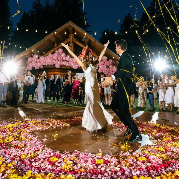 Bride and groom dancing at an outdoor wedding reception amid colorful flower petals