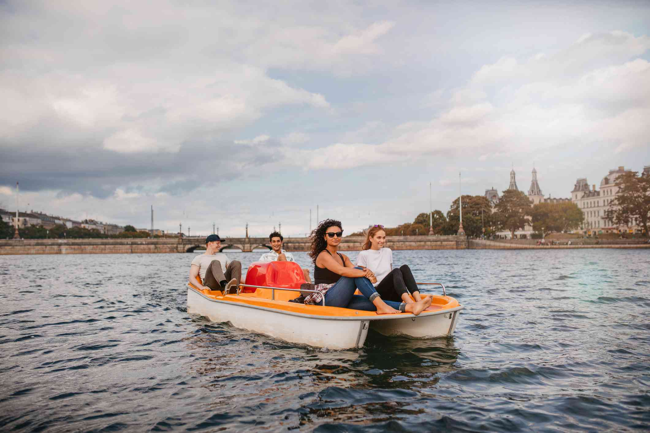 Two men pedaling a pedal boat on a lake while two women sit up front