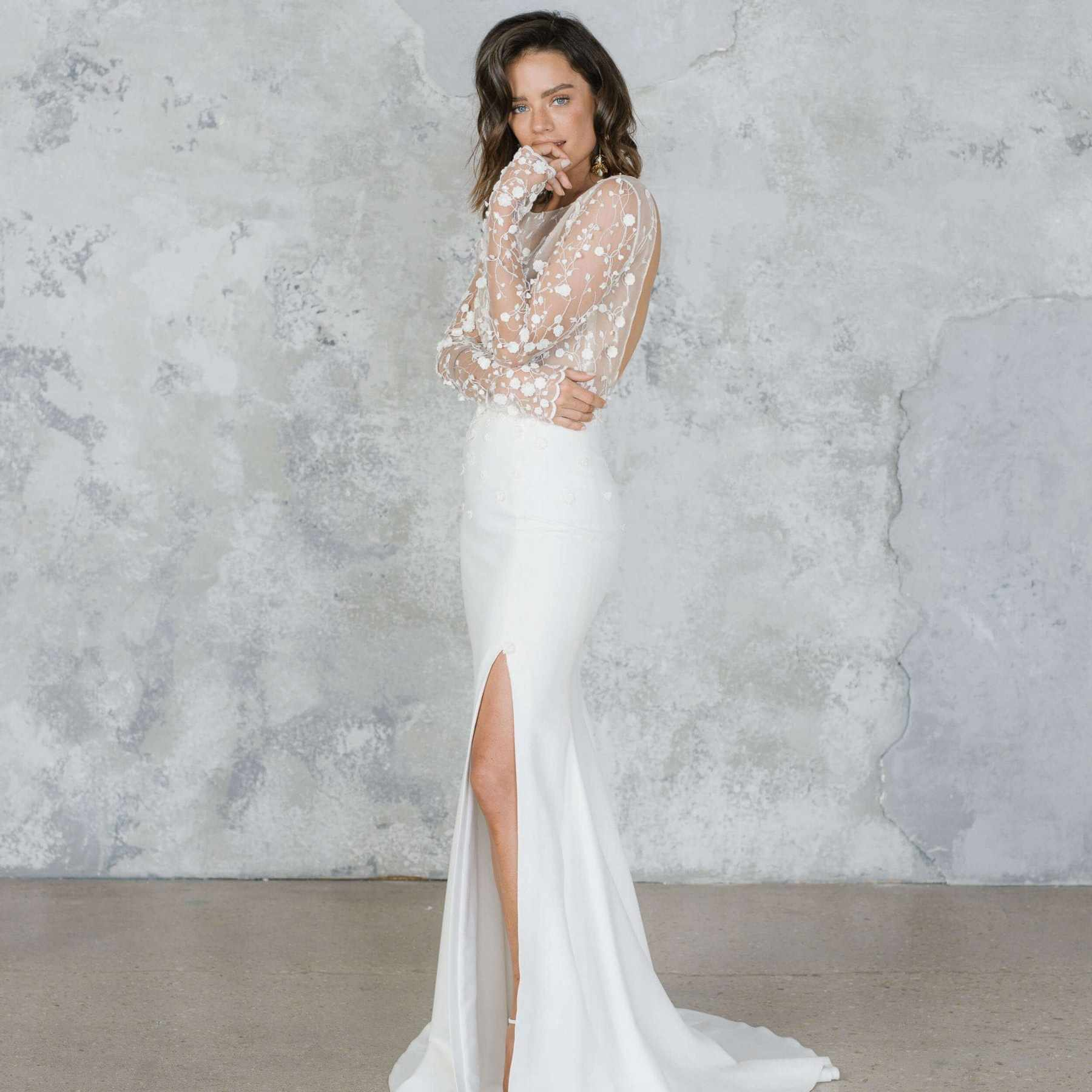 Model in floral embroidered illusion bodice with long sleeves wedding gown