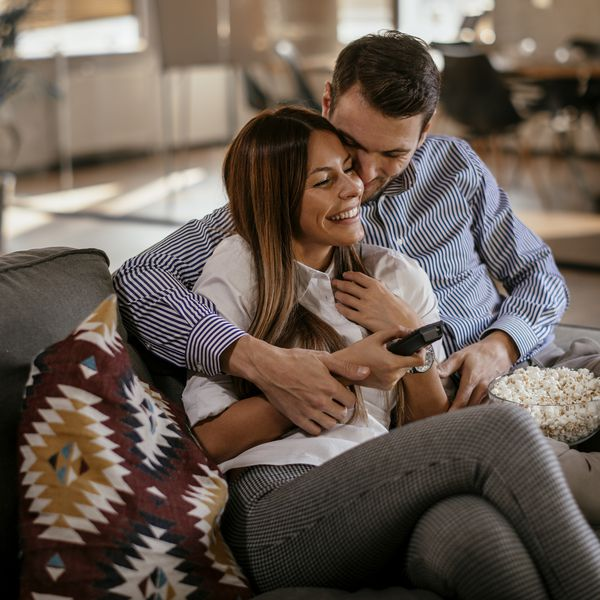 Man and woman hugging on couch