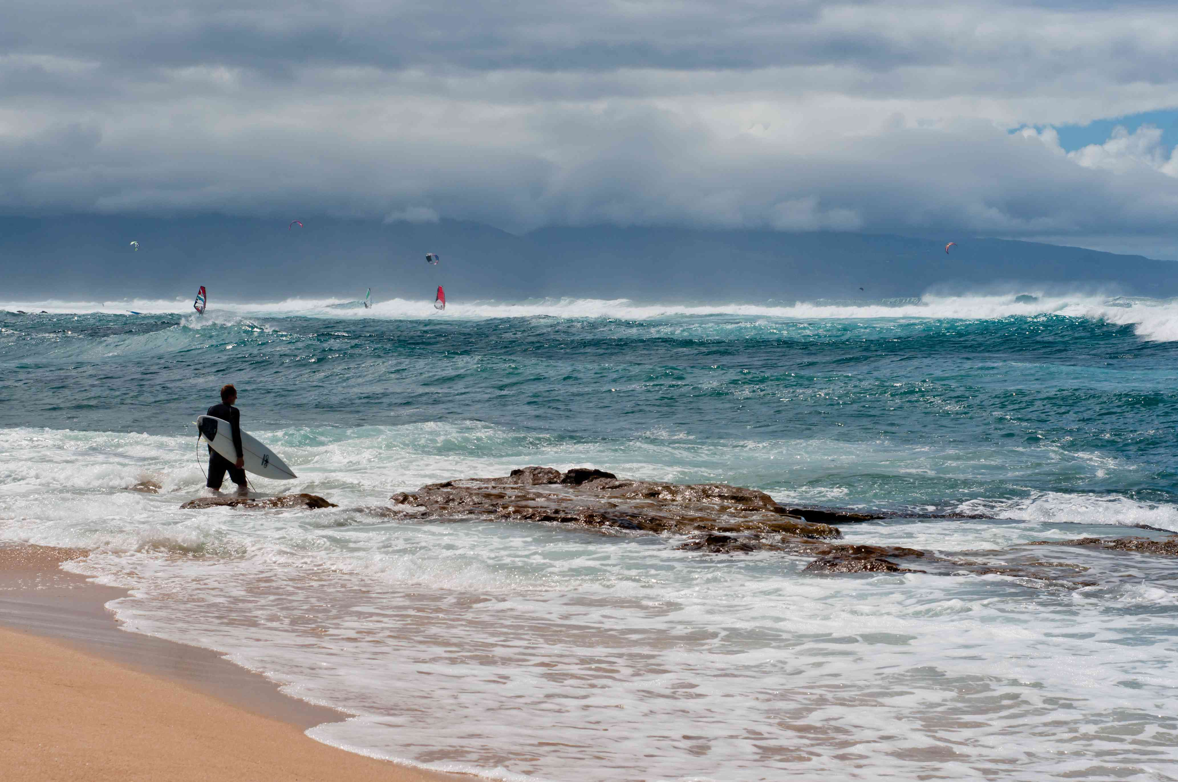 Surfer entering the ocean in Paia