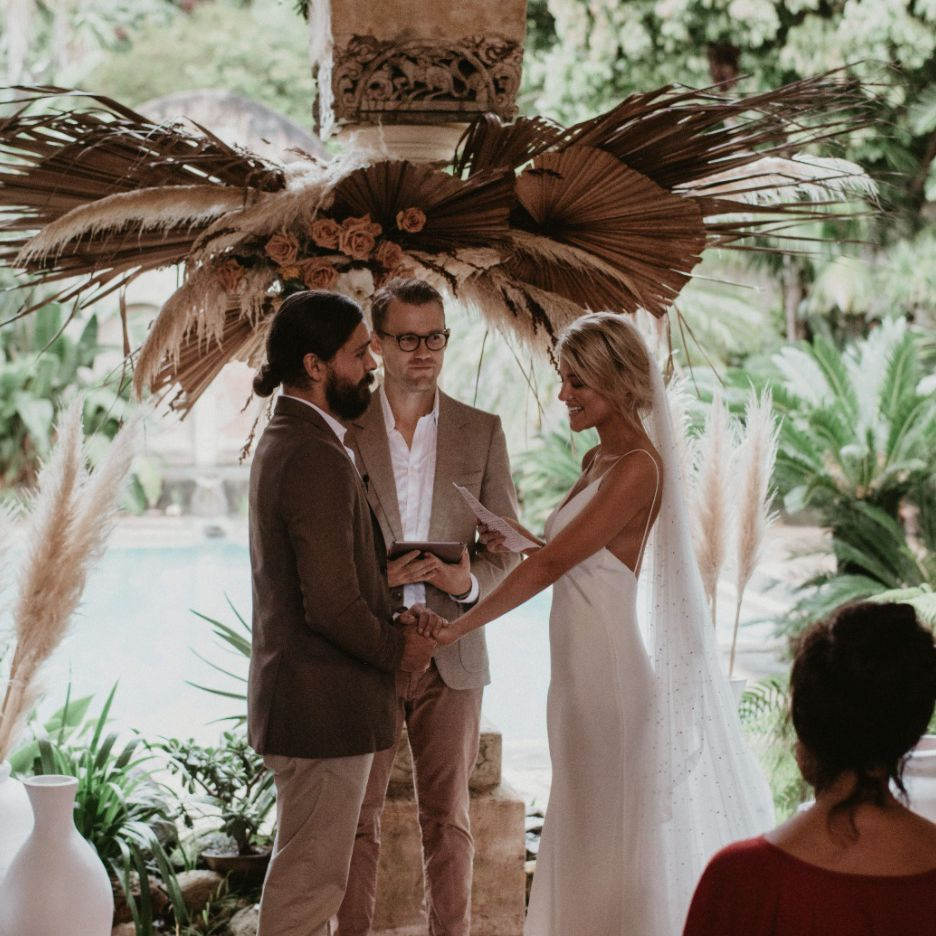 Newlyweds exchanging vows in front of backdrop of dried toffee roses, palms, and pampas grass