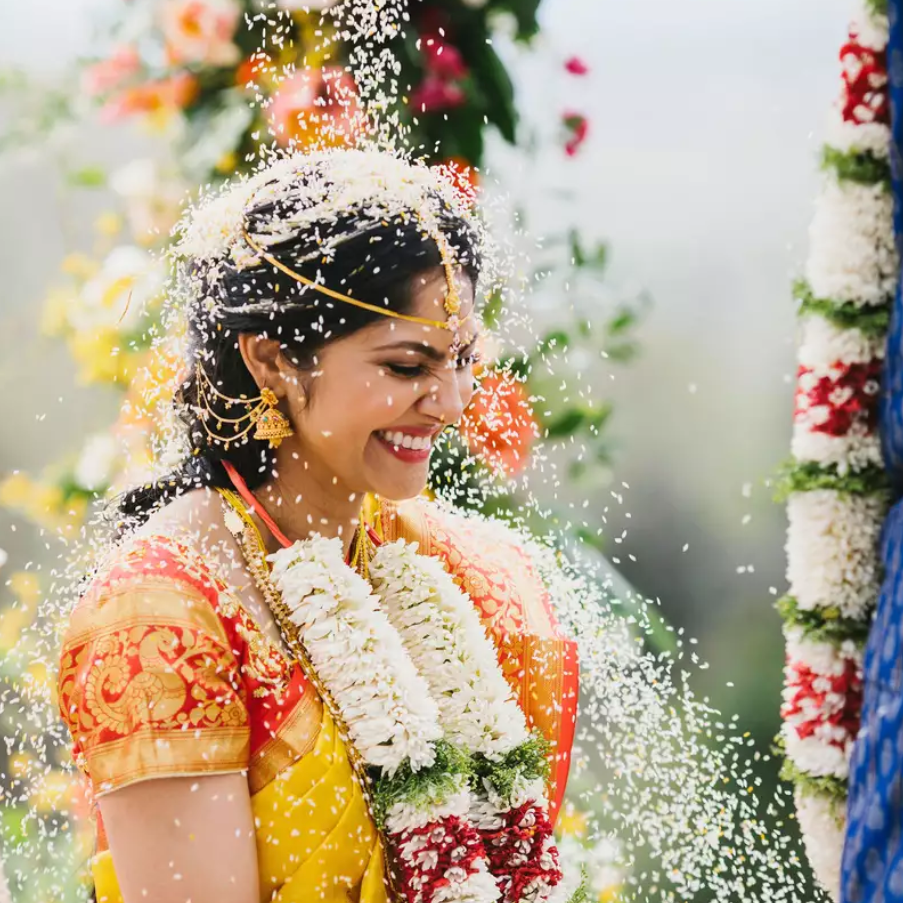 Indian bride being showered with turmeric rice