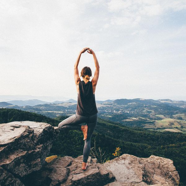 Rear View Of Woman Practicing Yoga On Rock At Mountain Against Sky