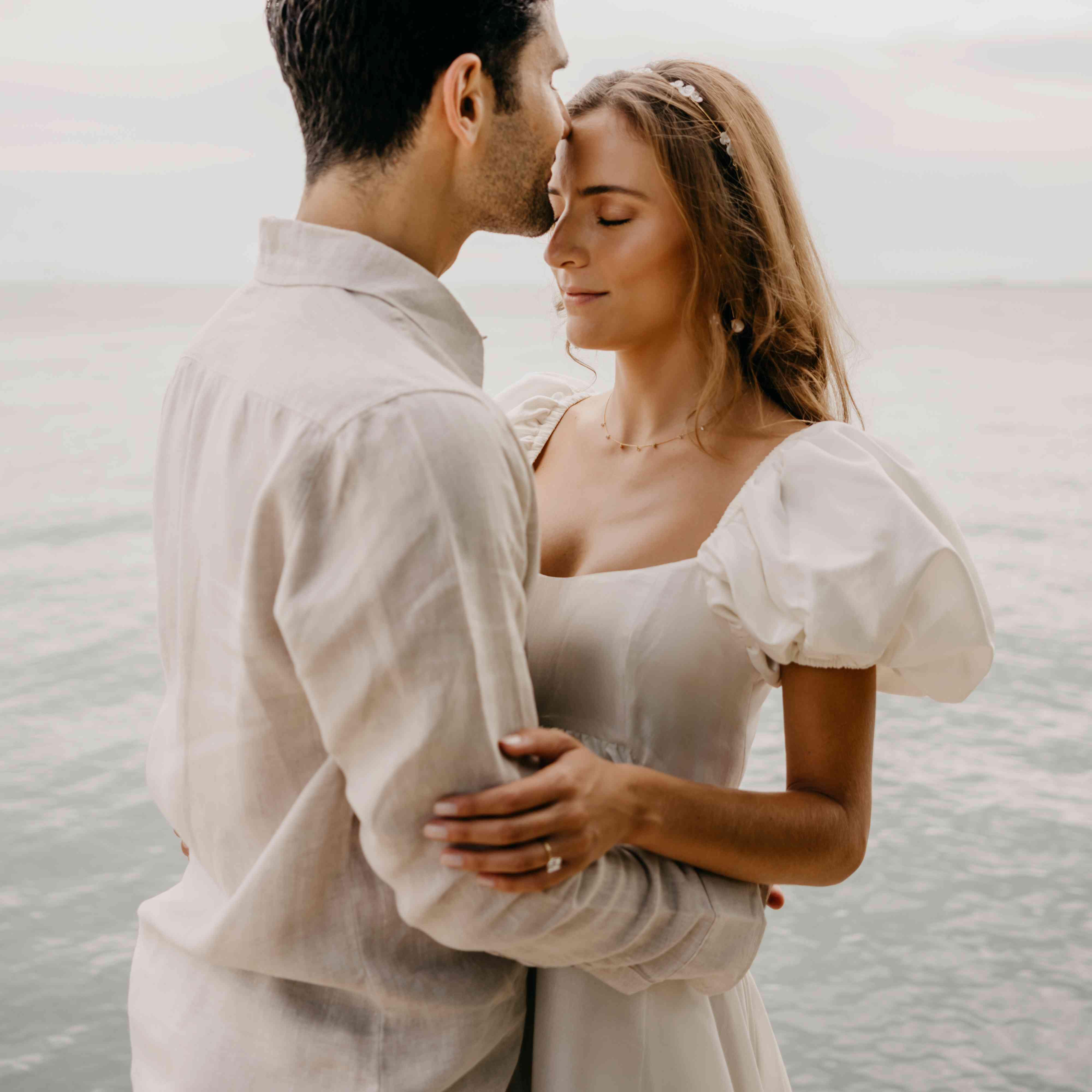 Couple embracing in front of ocean