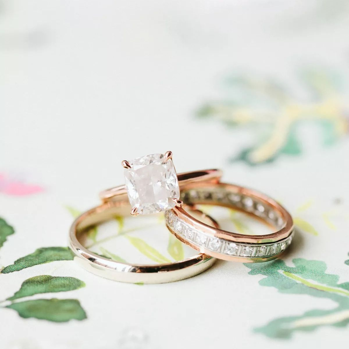 Cushion-cut engagement ring on rose gold band beside two wedding bands