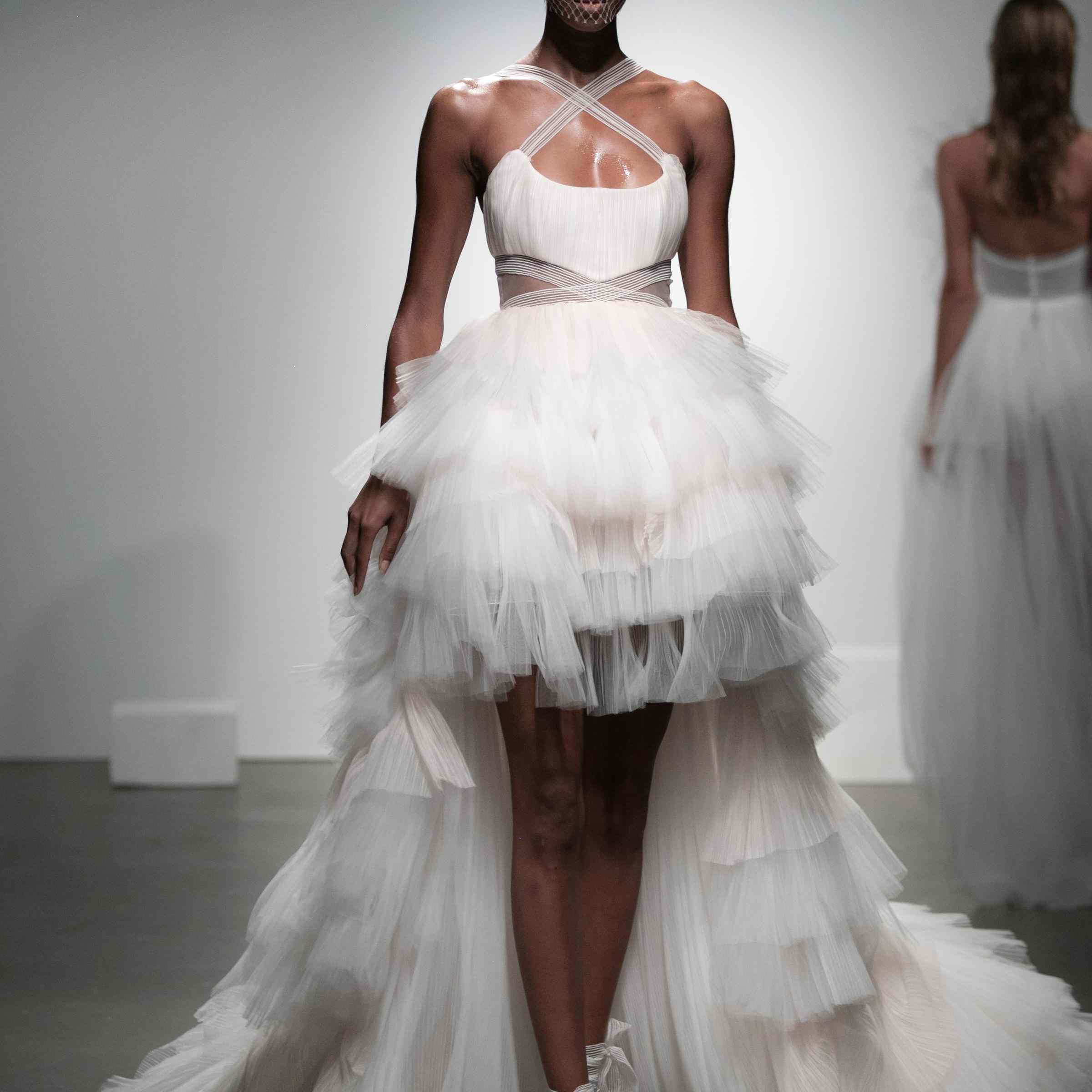 Model in flounced tulle dress with high-low hem and crisscrossed neckline