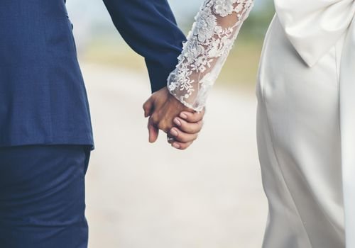 Close-up from behind bride and groom holding hands