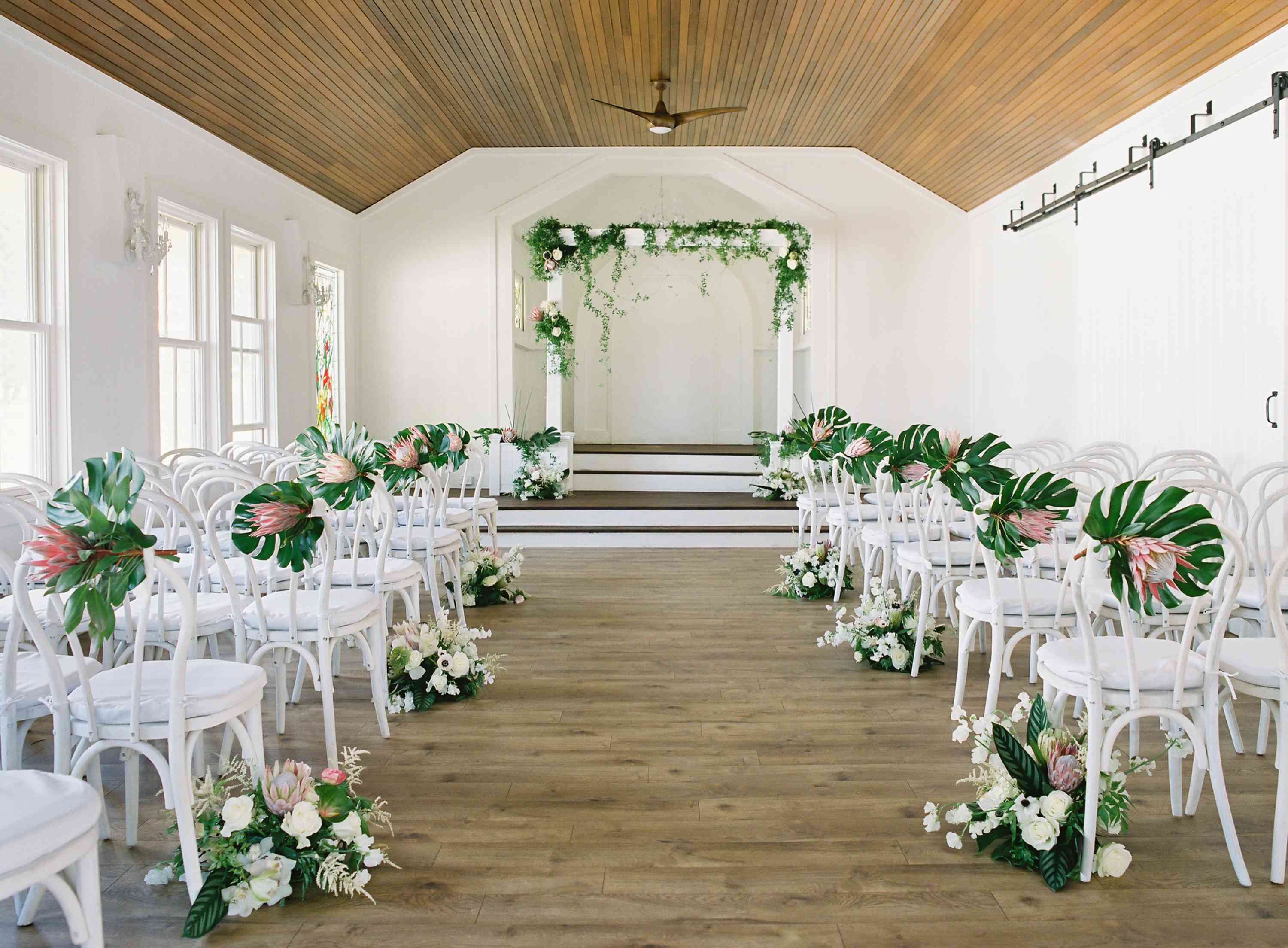 tropical maui wedding, white ceremony seating tropical florals