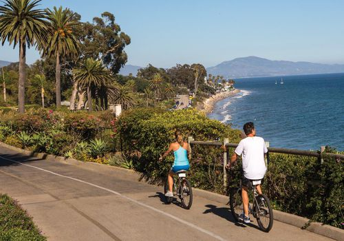 A woman and a man riding bikes alongside the ocean