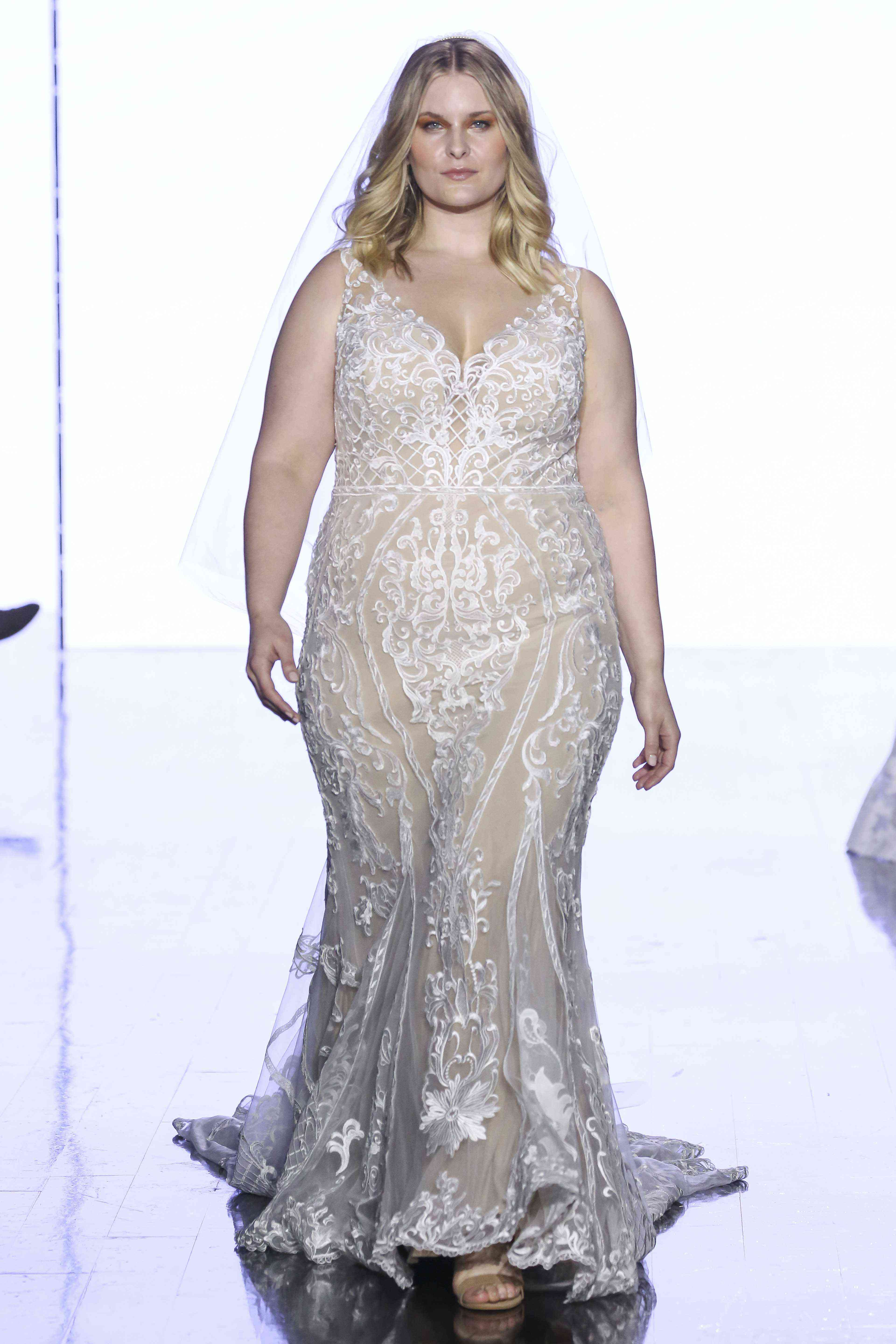 Model in V-neck fit-and-flare allover lace embroidered gown