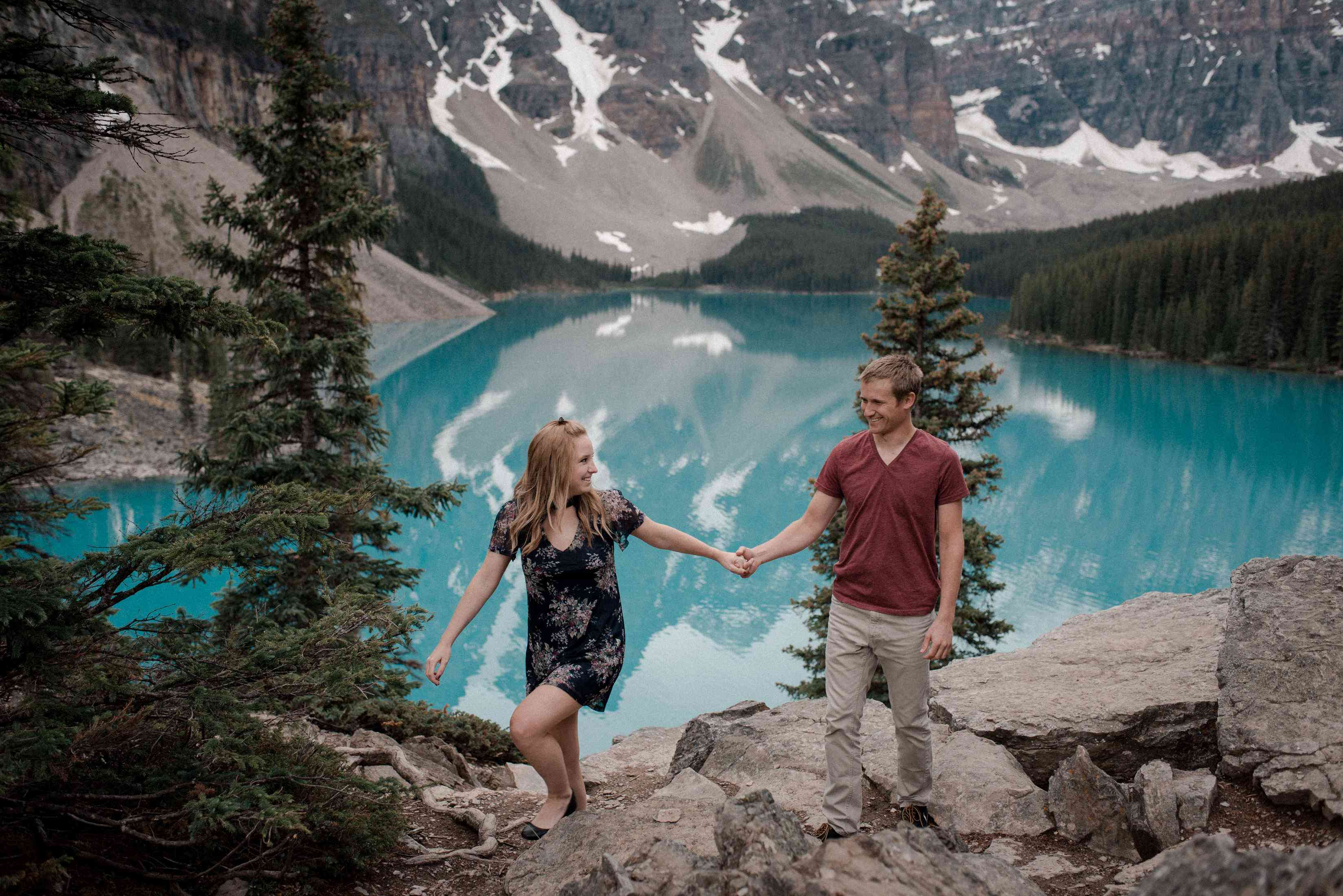 Couple holding hands with turquoise lake in background