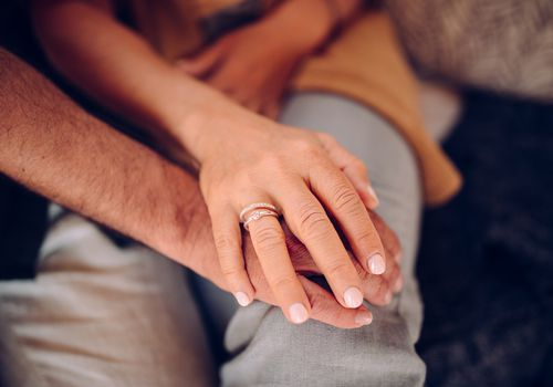 Woman's hand with engagement and wedding ring holding husband's hand