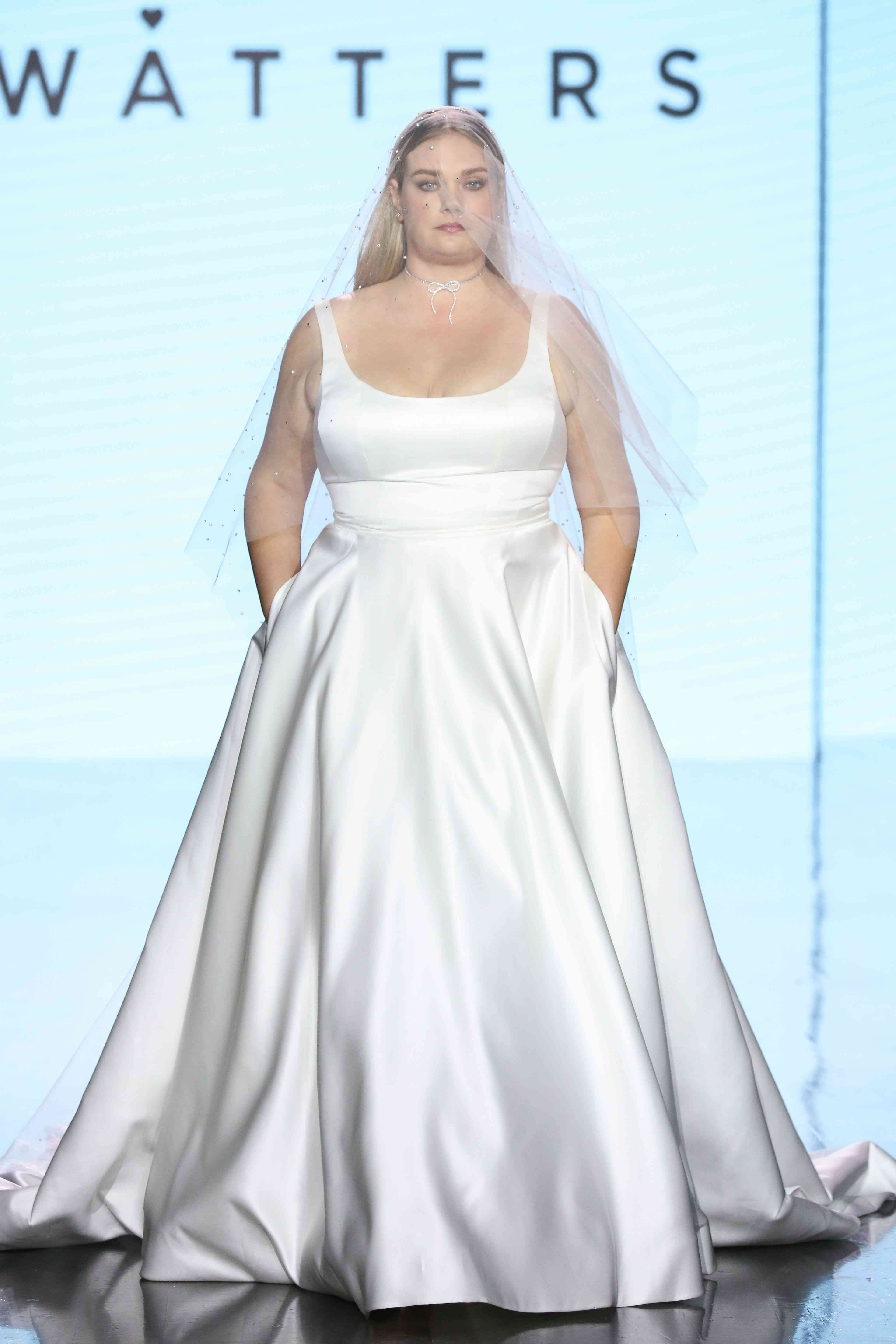 Model on runway in sleeveless scoop neck satin ballgown with skirt pockets