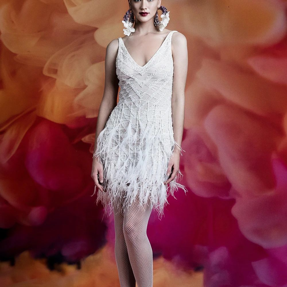 Model in V-neck short embroidered dress with feather skirt