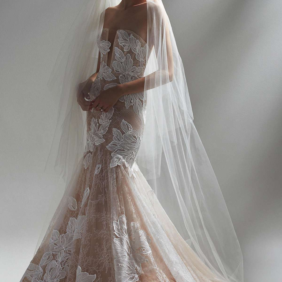 Model in sheer fit and flare wedding gown with floral cutouts