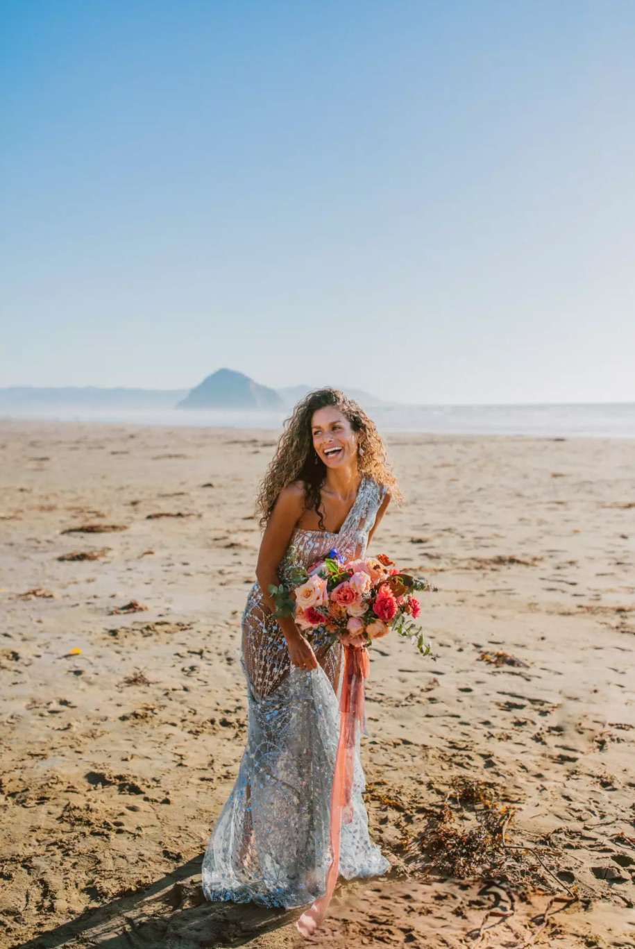 Bride with curly hair in the sand