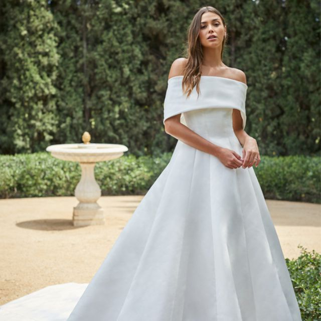 Model in white wedding gown with cuffed off-the-shoulder neckline