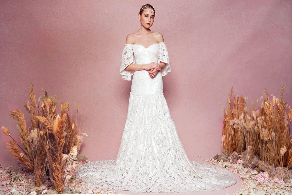 Model in lace off-the-shoulder gown with flutter sleeves and tiered skirt