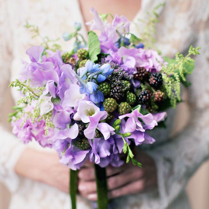 Bride holding a purple bouquet of blackberries, delphinium, sweet peas, freesia, stock, astilbe, trachillium, and scented geranium leaves.